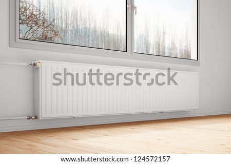 Central heating attached to wall with closed windows - stock photo