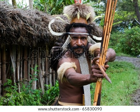 CENTRAL PAPUA, NEW GUINEA - JUNE 25: The warriorr of Dani Dugum tribe with an bow and an arrow aims in the photographer. Indonesia. Papua New Guinea. Village of people Dani Dugum. June 25, 2009. - stock photo