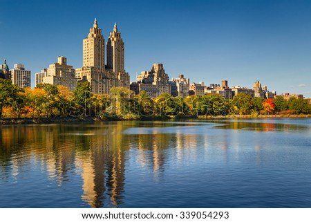 Central Park and Manhattan, Upper West Side with colorful Fall foliage. A clear blue sky and buildings of Central Park West reflecting in the Jacqueline Kennedy Onassis Reservoir. New York City. - stock photo