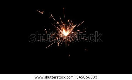 Centrally positioned firework sparkler burning isolated. Gun powder sparks shot against deep dark background - stock photo
