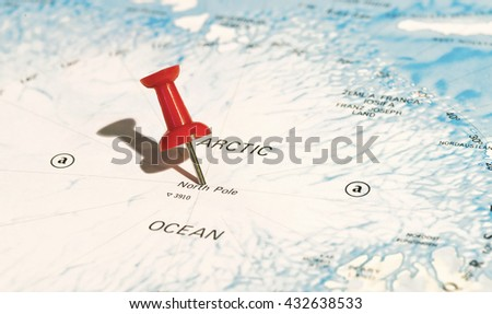 Centre of North Pole marked on map with red pushpin. Selective focus on the word North Pole and the pushpin. Pin casts harsh shadow to the left. - stock photo