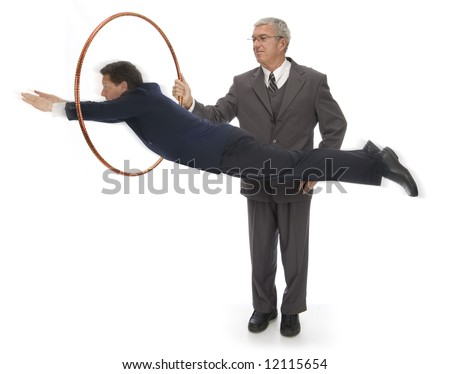 CEO holding up a hoop for his employee to jump through - stock photo