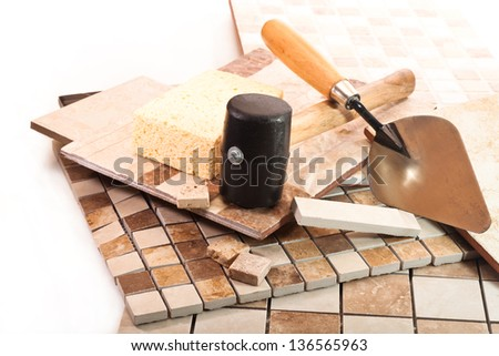 Ceramic and marble tile, trowel, a sponge and a rubber mallet on white background - stock photo