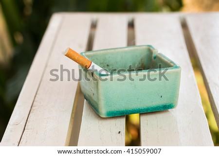 ceramic ashtray and cigarettes - stock photo
