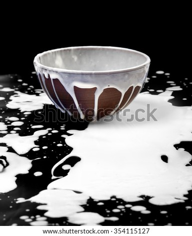 Ceramic bowl and spilled milk in black background - stock photo