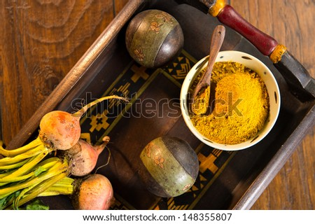 Ceramic bowl filled with yellow curry powder with a wood spoon on a decorative wooden tray. The tray is shot on a wood surface.  Beet roots are also pictured. - stock photo