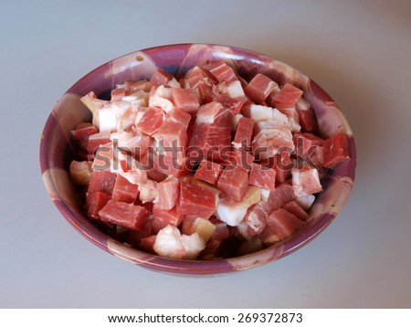 Ceramic bowl full of raw meat pieces close up - stock photo
