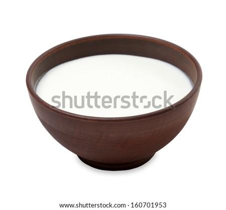 Ceramic bowl with milk on white background - stock photo