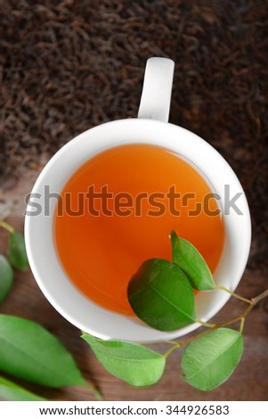 Ceramic cup of tea with scattered tea leaves around on wooden background - stock photo