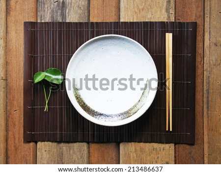 ceramic dish (plate) and chopsticks on bamboo mat. - stock photo