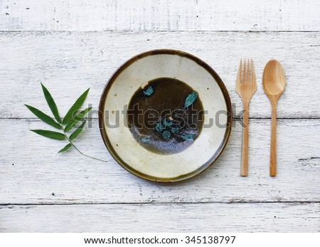 Ceramic dish(plate) and wooden spoon,wooden fork on wooden table.Flat lay - stock photo