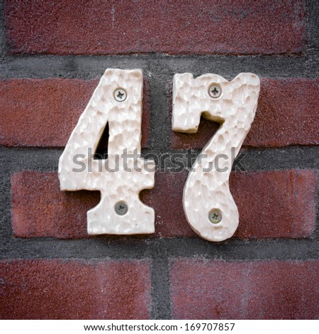 ceramic house number forty seven on a brick wall. - stock photo