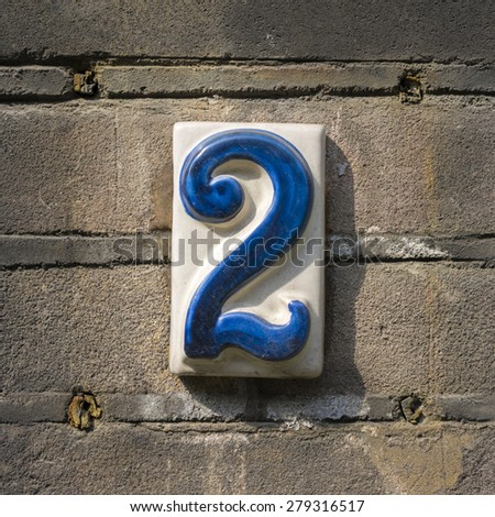 ceramic house number two on a brick wall. - stock photo