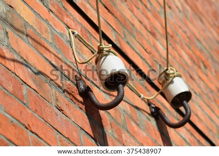 Ceramic insulators on the wall. Connection wiring. - stock photo