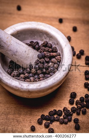 ceramic mortar and pestle full with aromatic black peppercorns - stock photo