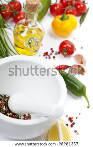 Ceramic Mortar with Pestle, fresh spices and vegetables - stock photo