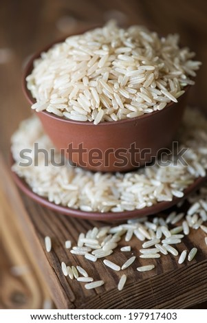 Ceramic pialat with raw brown rice kernels, close-up - stock photo