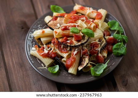 Ceramic plate with pasta alla Norma on a rustic wooden surface - stock photo