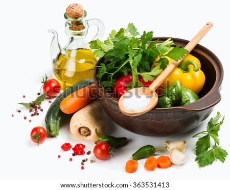 Ceramic pot surrounded by scattered fresh vegetables and ingredients for vegetable dish isolated on white background. - stock photo