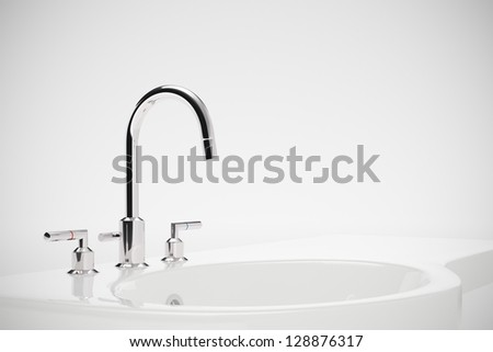 Ceramic sink with chrome fixture on white background - stock photo