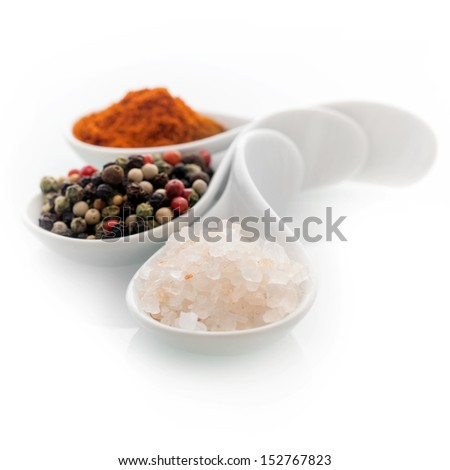 Ceramic spoons filled with natural Himalayan rock salt, whole dried black peppercorns and hot red cayenne pepper on a white background - stock photo