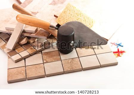Ceramic tile, trowel, a rubber hammer, sponge, crosses on a white background - stock photo