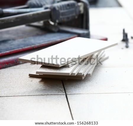 ceramic tiles and trowel for repairs - stock photo