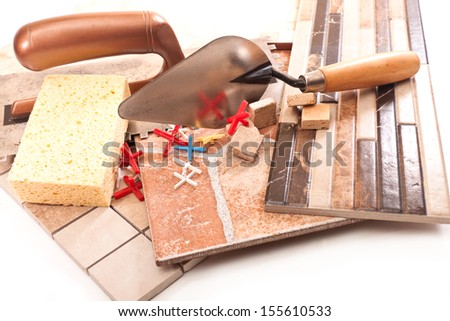 Ceramic tiling to walls and floor, trowel, sponge, crosses on a white background - stock photo