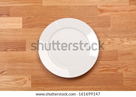 Ceramic white plate on wooden background  - stock photo