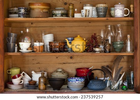 ceramics and kitchen equipment on rustic and country style wooden shelves - stock photo