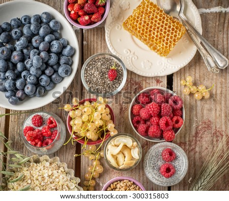 cereal and various delicious ingredients for breakfast and wooden background, top view - stock photo