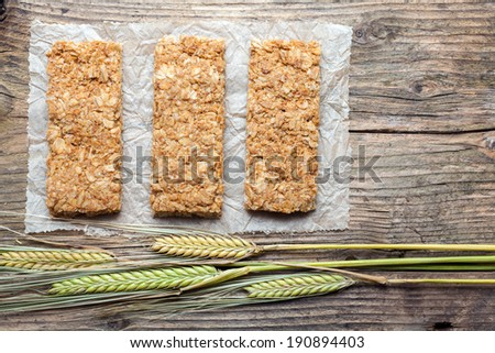 Cereal bars and dry wheat on a wooden table - stock photo