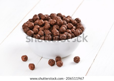 Cereal chocolate balls on white wooden table - stock photo