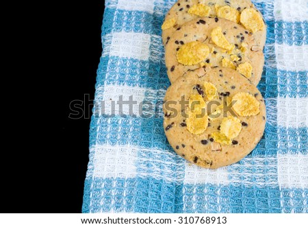 Cereal cookies on blue checkered tablecloth selective focus isolate on black background. - stock photo