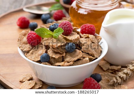 cereal flakes with fresh berries, honey and milk for breakfast, close-up - stock photo