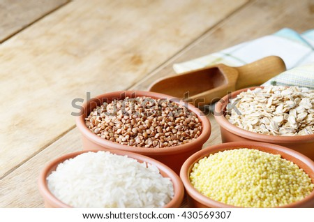 Cereal grains set in ceramic bowls on wooden table - stock photo