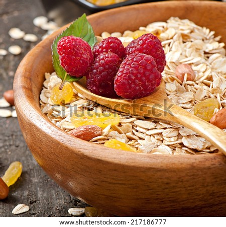 Cereal in a wooden bowl, with fresh raspberries and raisins - stock photo