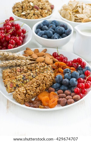 cereal muesli bars, fresh and dried fruit for breakfast, vertical, closeup - stock photo