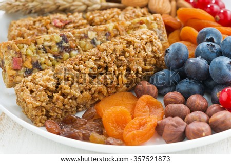 cereal muesli bars, fresh and dried fruit on a white plate, closeup, horizontal - stock photo