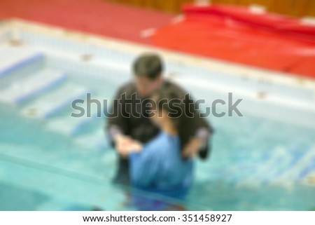 Ceremony of baptism blurred background. person christ babies priest baptism religion emotions child candle water indoors image christianity events new Birth victory death New life pond dip Dead to Sin - stock photo