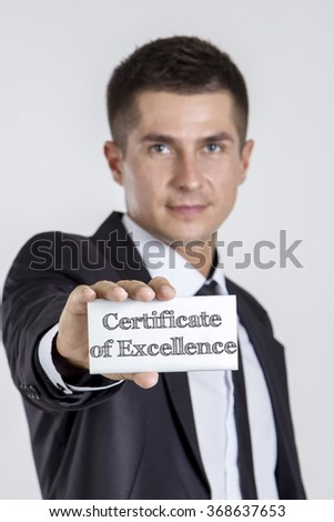 Certificate of Excellence - Young businessman holding a white card with text - vertical image - stock photo