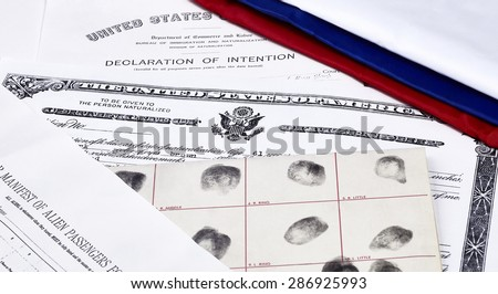 Certificate of US Citizenship, declaration of intention, fingerprint card and passenger manifest with red, white and blue ribbon - stock photo