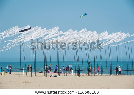 CERVIA, ITALY - APRIL 27: Sky full of flags for International Kite Festival on April 27, 2012 in Cervia, Italy. This Festival brings together kite flyers from all over the world every year since 1981. - stock photo