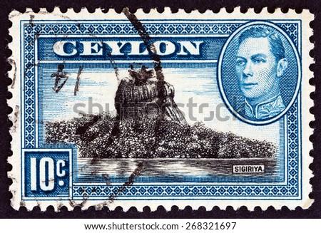 CEYLON - CIRCA 1938: A stamp printed in Ceylon shows Sigiriya (Lion Rock) and King George VI, circa 1938.  - stock photo