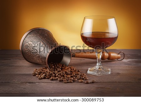Cezve with coffee beans and glass of whiskey. - stock photo