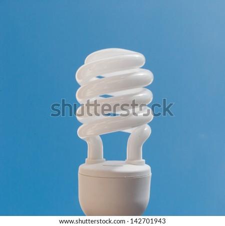 cfl bulb on blue sky background - stock photo