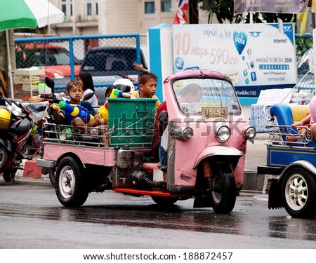 Chachoengsao Province 13 April 2014: Thai children on Tuk-Tuk wearing colorful clothes celebrate Songkran festival splashing water with bowls and water spray guns on the street in cities of Thailand  - stock photo