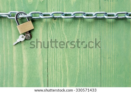 Chain and lock on  green wooden background - stock photo
