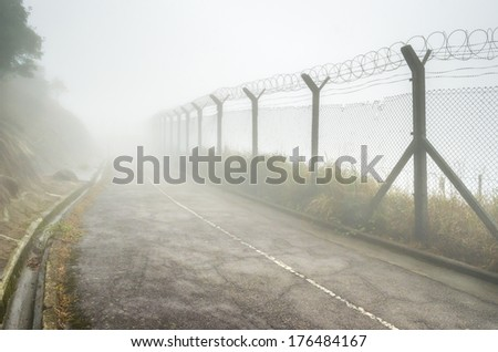 Chain-link fencing and Barbed wire in Fog - stock photo