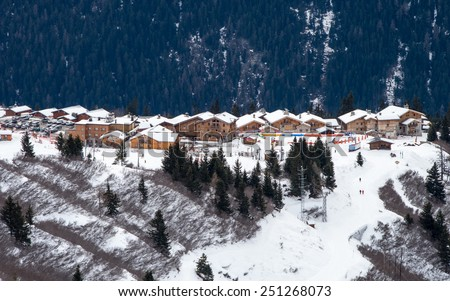 Chain of alpine chalets with restaurants, ski services and shops in La Rosiere ski resort in French Alps, surrounded by snowy coniferous mountain forest  - stock photo
